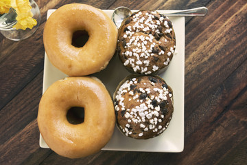 Two stacked sugared donuts and muffins