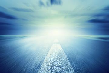 Long empty asphalt road towards light. Motion, speed