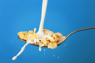 milk splashing into spoon with cornflakes over blue
