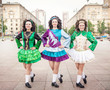 Three women in irish dance dresses posing outdoor