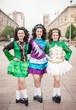 Three women in irish dance dresses posing outdoor