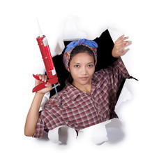 woman with caulking gun tool in hole of paper