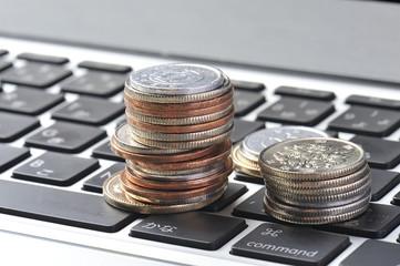 パソコンのキーボードの上に置かれたコイン