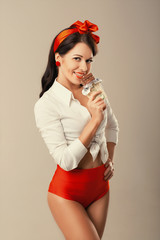 Pinup woman with chocolate in studio. Back to 1950s.