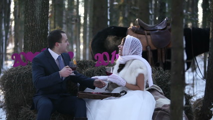 Newlyweds in the winter forest with a horse