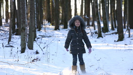 The child is in the winter woods.