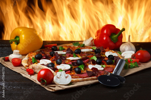 Fototapeta Hot pizza with oven fire on background