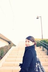 階段を上る黒いコートの女性