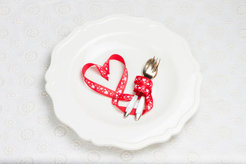 heart of ribbons on a plate with cutlery