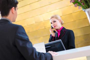 Rezeptionistin checkt Mann bei Anreise im Hotel ein