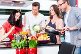 Fototapety Freunde kochen Pasta und Fleisch zuhause in Küche