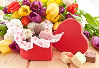 Verschiedene Pralinen und bunte Tulpen