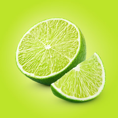 Half and slice of lime citrus fruit on green background