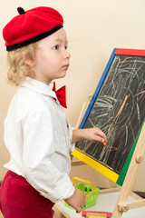 Cute child girl drawing chalk on easel in suit of artist