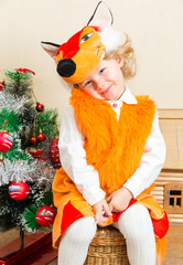 Little child girl dressed in fox suit near Christmas tree