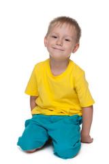 Blond preschool boy sits on the floor
