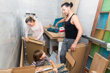 parents with son unpacking boxes