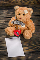 Teddy Bear, heart lock on old wood background.