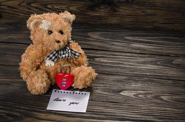 Teddy Bear, heart lock on old wood background.