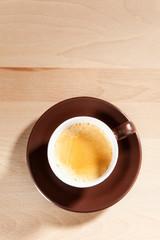 Eine Tasse Kaffee steht auf einem Holztisch