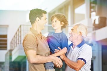 Vater trägt Sohn neben Großvater im Sommer