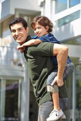 Vater trägt seinen Sohn auf dem Rücken