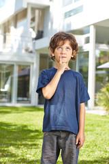 Nachdenkliches Kind steht im Garten