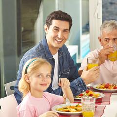 Vater und Tochter essen mit Großvater