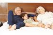 Paar Senioren mit Enkel auf Bett