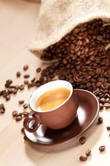 Eine Tasse Kaffee und geröstete Kaffeebohnen