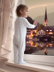 Little boy looking at beautiful evening view in Hallstatt city.