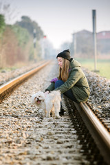 Girl with dog playing on the railroad
