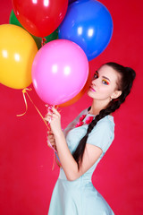 Portrait of a young attractive woman holding bunch of balloons