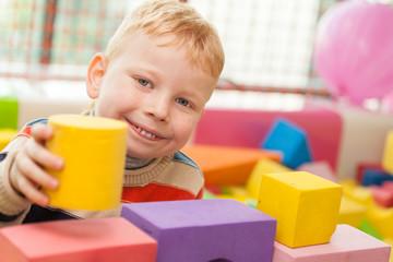 Little boy play construction set