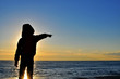 Silhouette of a boy pointing out the sea