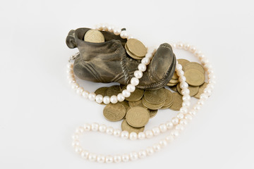 Old bronze shue filled with gold coins and pearls on white
