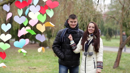 loving couple standing near a multi-colored hearts on Valentine'