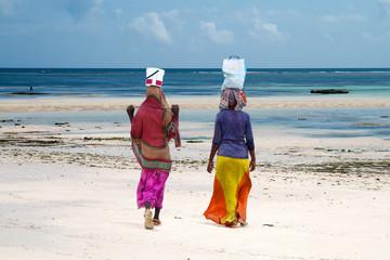 Women holding goods on head at the beach, Zanzibar island