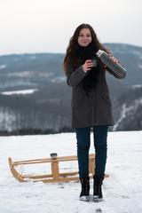 femme assise sur luge en paysage enneigé