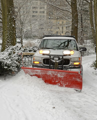 Truck plowing snowy road after snowstorm