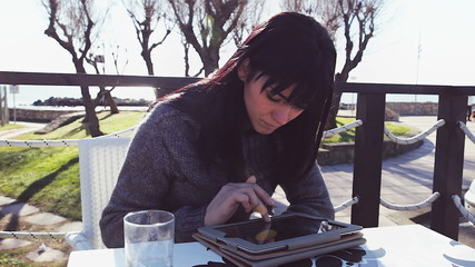 Beautiful girl writing email with tablet in coffee shop