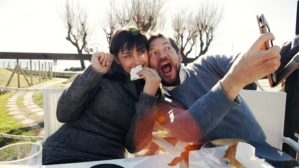Couple having breakfast outdoors taking selfie with tablet funny