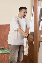 Vertical image of painter while observe a detail on canvas