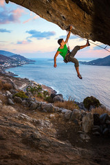 Rock climber on overhanging cliff at sunset