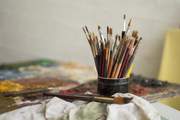 Painting brushes in black jar on plank as a palette