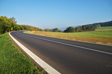 Empty asphalt road in countryside, bend of road