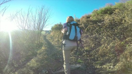 Woman hiking on mountain trail waiting for teammate