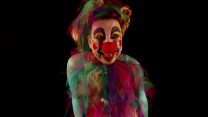 dancing clown with balloons in front of black
