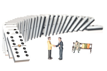 Domino effect with two miniature businessmen shaking hands