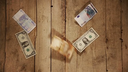 moneyrain with a lot of currencies on a wooden background